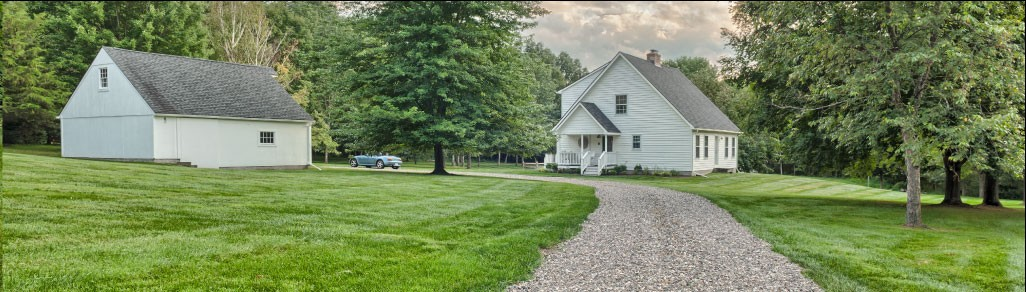 Well manicured lawn with gravel path leading to home