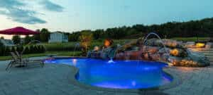 rock outcroppings on the side of lit-up swimming pool